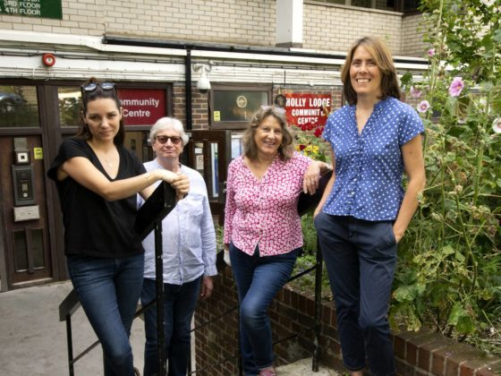 Three white women and one white man stand in front of a block of flats