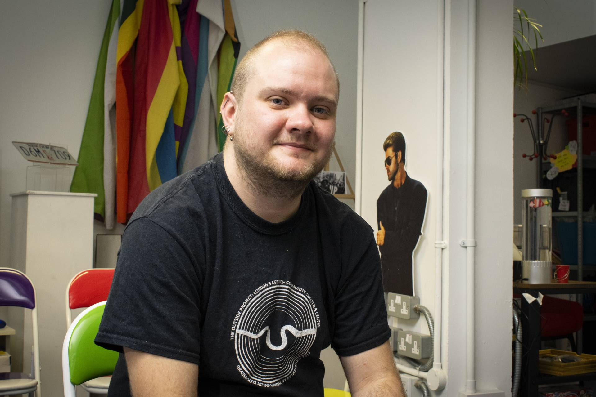 A white man with close cropped blonde hair and ear piercings, wearing a black T-shirt smiles for the camera