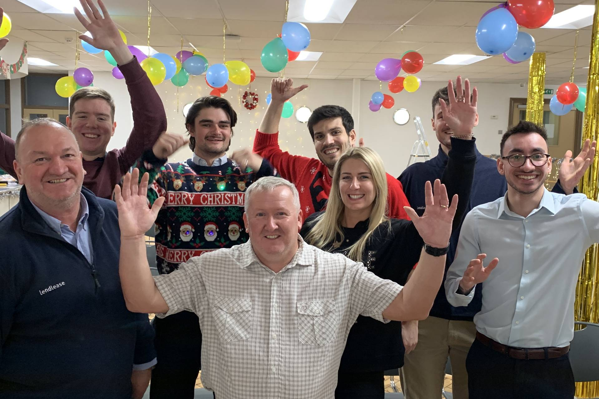 A group of people in an office decorated with ballons and Christmas decorations raise that hands and smile