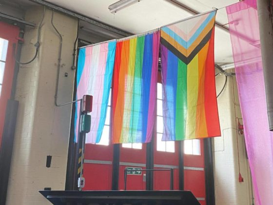 Image of Pride, trans and LGBTQIA+ flags hanging in a spacious hall
